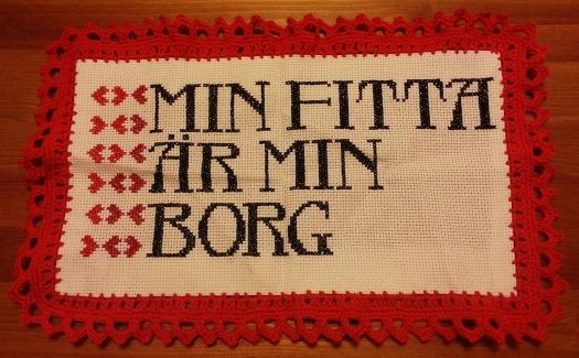 """Korsstygnsbroderi med texten """"Min fitta är min borg"""""""